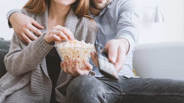 para je popcorn i ogląda telewizję