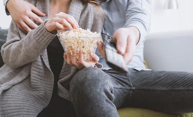mężczyzna i kobieta jedzą popcorn