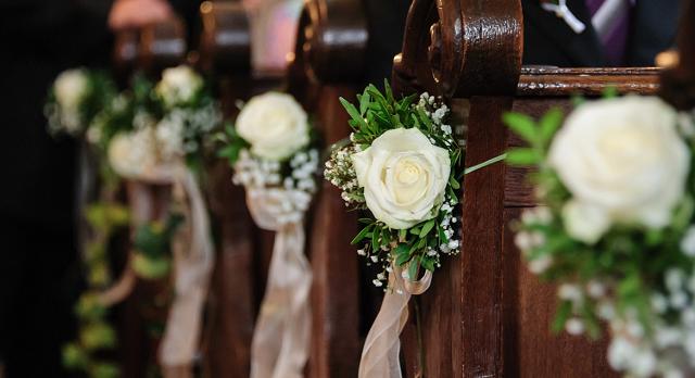 kwiaty przy ławkach w kościele