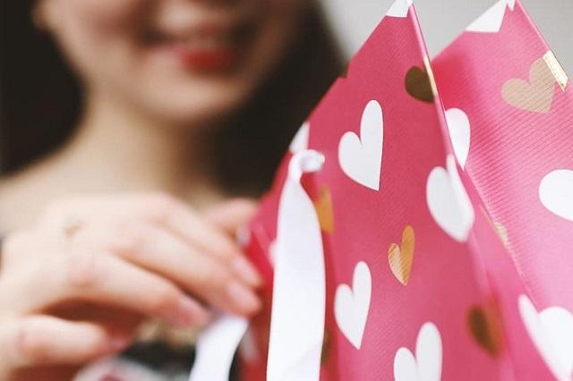 uśmiechnięta kobieta zagląda do torby z prezentami