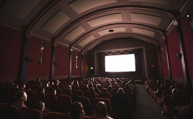 sala kinowa z małym ekranem i dużo ludzi