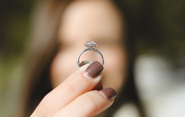 kobieta trzyma w dłoni pierścionek zaręczynowy