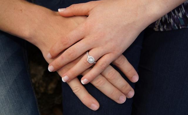 dwie dłonie splecione na jednej widnieje pierścionek zaręczynowy