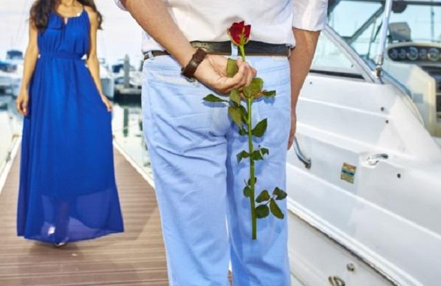 mężczyzna w niebieskich spodniach z różą za plecami