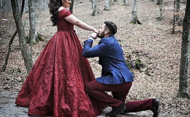 mężczyzna w niebieskiej marynarce klęczy przed kobietą w czerwonej sukience