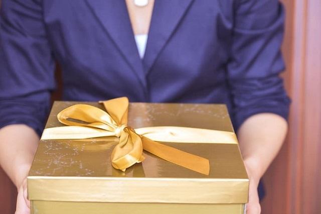 kobieta trzyma złote pudełko