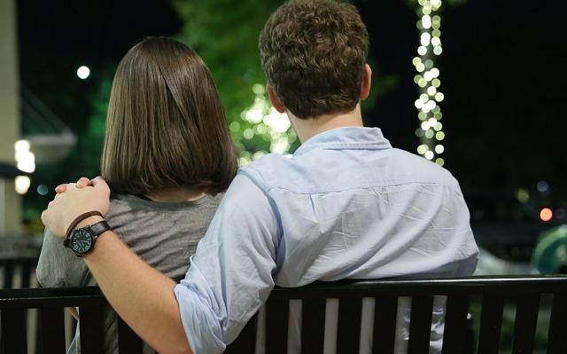 zakochani siedzą tyłem na ławce i patrzą przed siebie