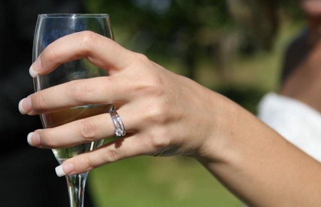 kobieca dłoń z pierścionkiem zaręczynowym trzyma kieliszek