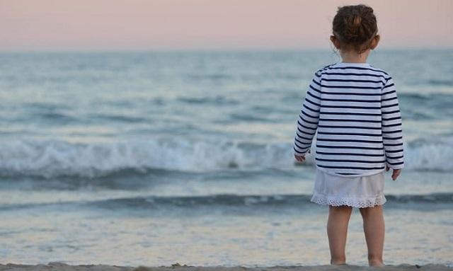 małe dziecko stoi przy morzu i zachodzi słońce
