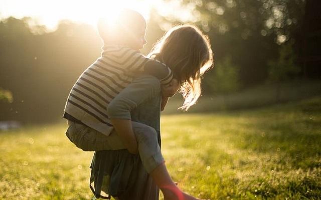 kobieta z dzieckiem na plecach