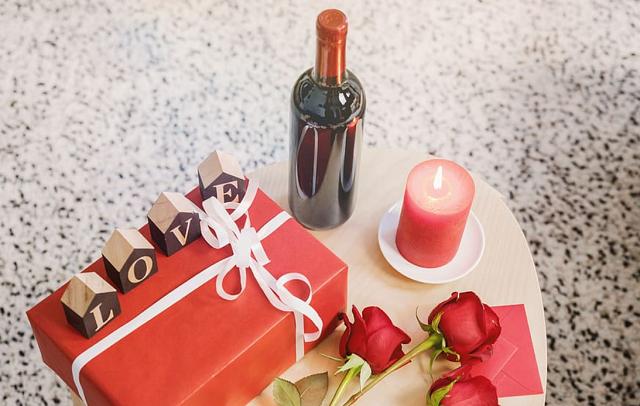 czerwona wino na stole z czerwonym prezentem i świeczką