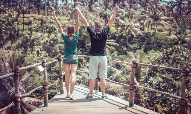 chłopak i dziewczyna stoją tyłem z uniesionymi rękoma
