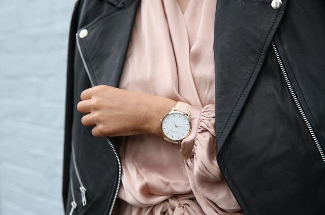 beżowa bluzka, czarna ramoneska i złoty zegarek na opalonej dłoni