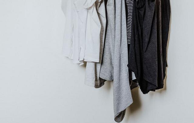 białe koszulki, czarne i szare, które wiszą na wieszaku