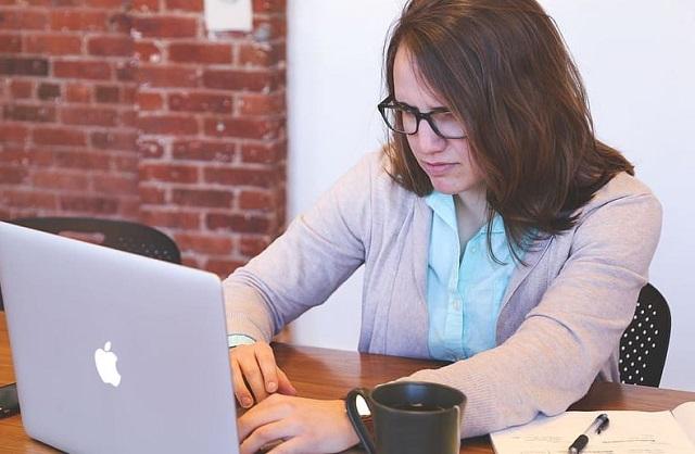 kobieta w rozpuszczonych włosach i w okularach przed komputerem