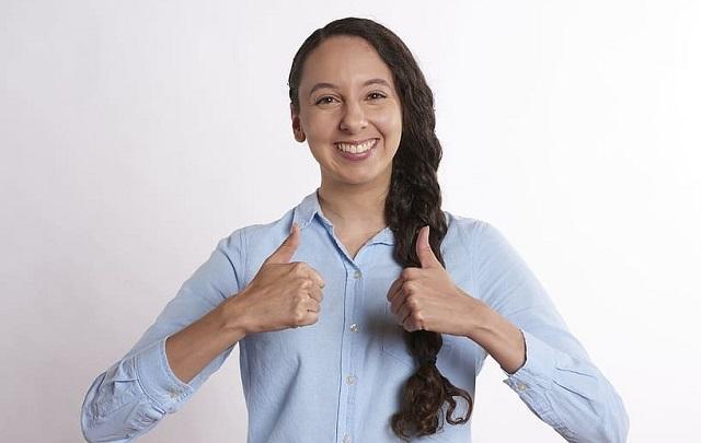 uśmiechnięta naturalna kobieta w warkoczu pokazuje kciuki
