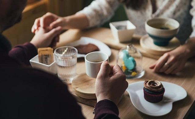 para trzyma się za ręce przy stole w czasie jedzenia deseru