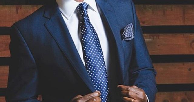 mężczyzna w skórzanych rękawiczkach i granatowym garniturze i krawacie w kropki