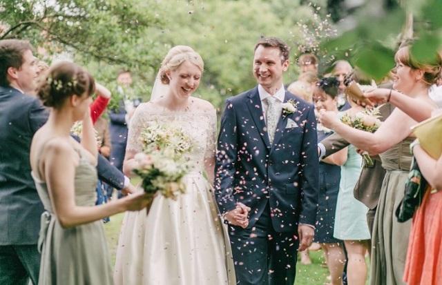 uśmiechnięta młoda para i goście weselni którzy rzucają w nich płatkami kwiatów