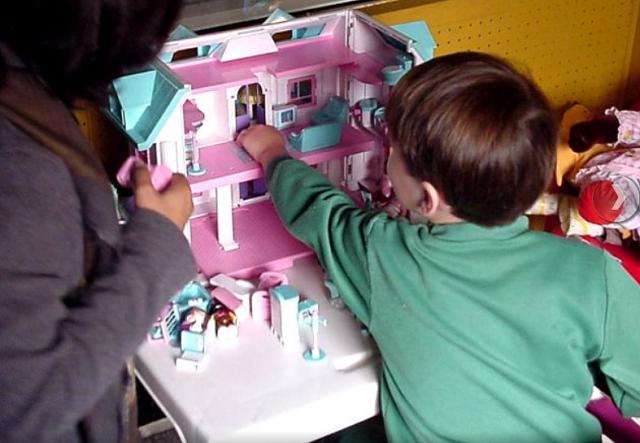 dziecko bawi się lalkami w domku dla lalek