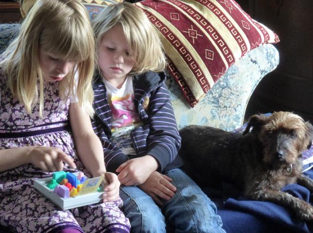 dziewczynka i chłopczyk bawią się siedząc na kanapie
