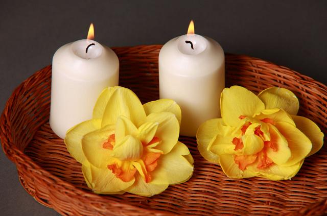 dwie białe świeczki palące się na wiklinie obok dwóch żółtych kwiatków