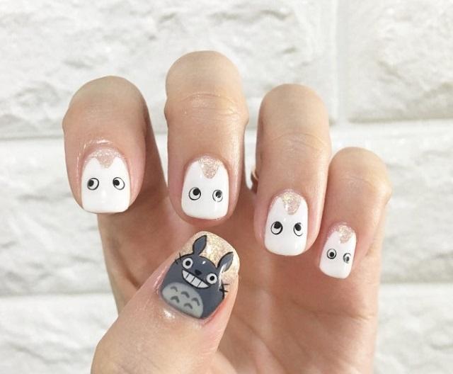 dłoń z pomalowanymi paznokciami na których są wzory w potworki