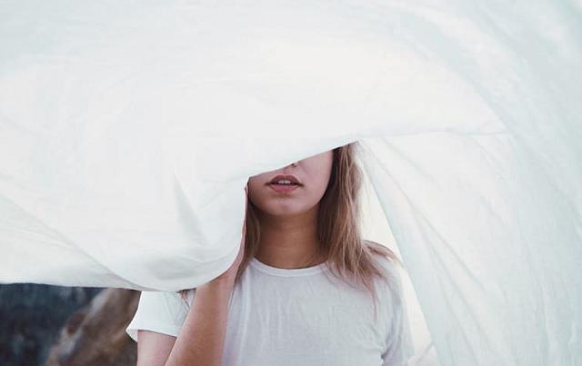 dziewczyna w białym t-shircie zasłonięta prześcieradłem wiszącym na sznurku