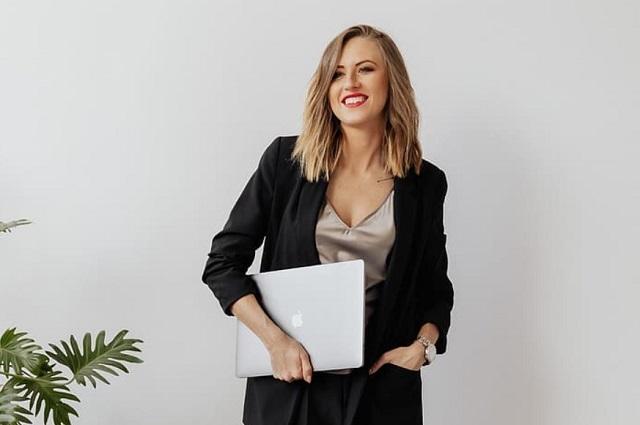 uśmiechnięta blondynka w czarnej marynarce stoi a w dłoni trzyma laptopa