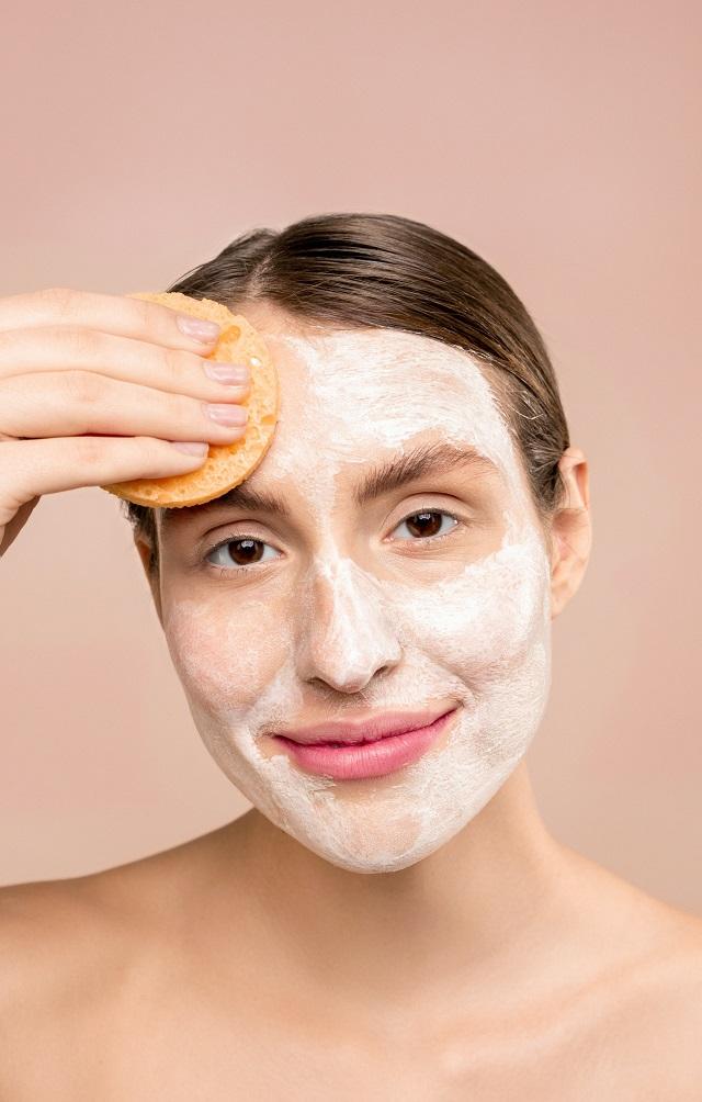 naturalna kobieta ma żel na twarzy i gąbką go wciera w czoło