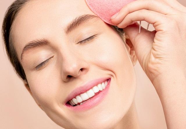 uśmiechnięta kobieta dotyka się gąbką twarzy i ma zamknięte oczy