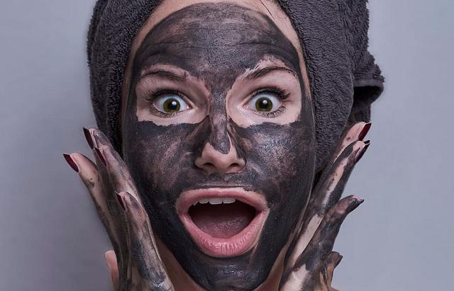 zdziwiona młoda kobieta z czarną maseczką na twarzy i ręczniku na głowie