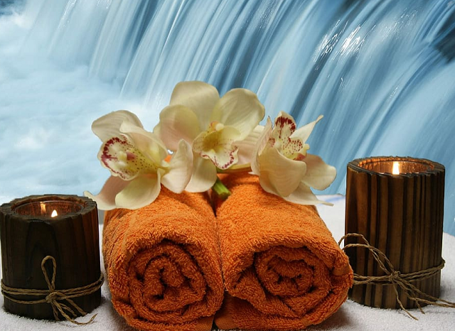 pomarańczowe ręczniki a na nich kwiaty i obok zapalone świeczki