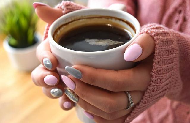 kobieta z szaro-różowym manicure trzyma kubek kawy