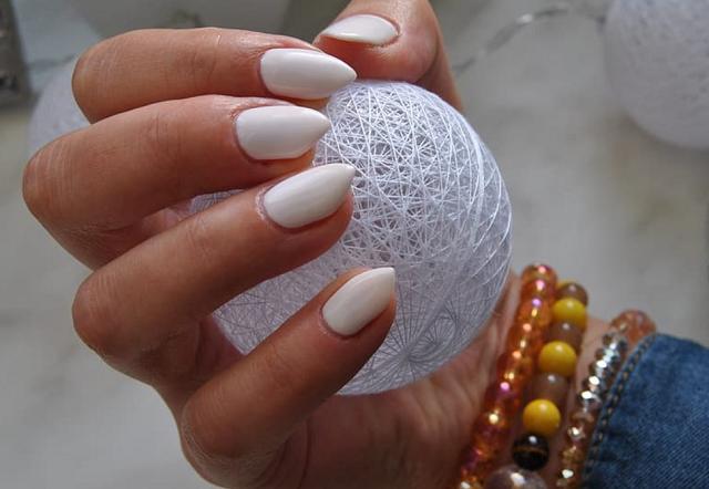 dłoń z paznokciami pomalowanymi na biało trzyma kulę