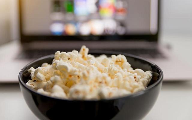 popcorn w czarnej miseczce przez telewizorem