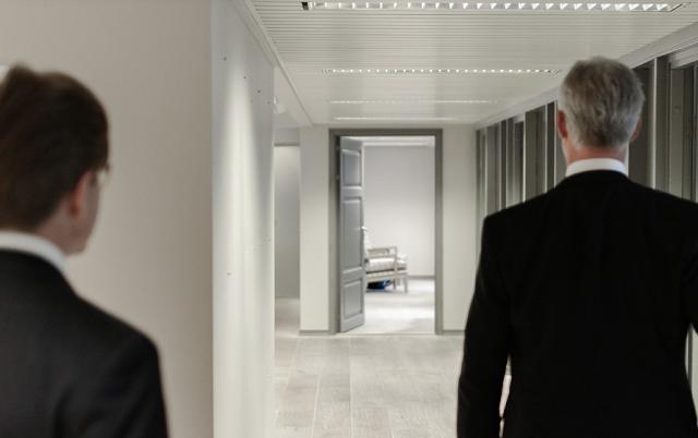 dwóch mężczyzn idzie przez korytarz bardzo jasny