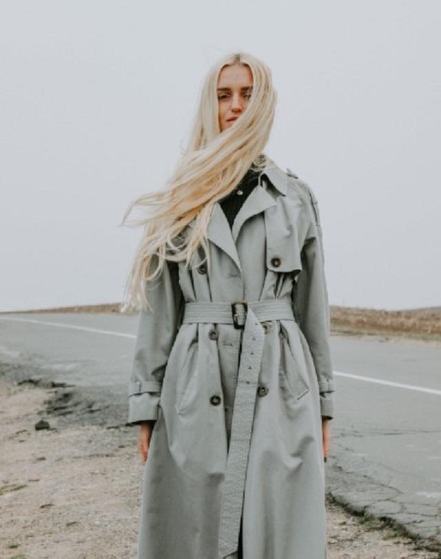 blondynka w rozpuszczonych włosach stoi na tle drogi w jasnym płaszczu