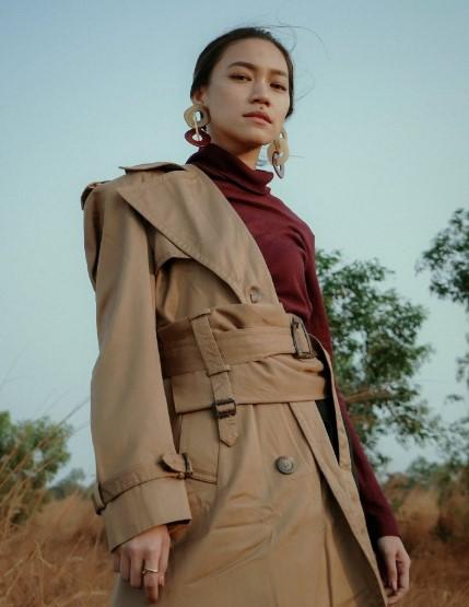brunetka w spiętych włosach stoi w płaszczu do połowy założonym i ceglastym golfie