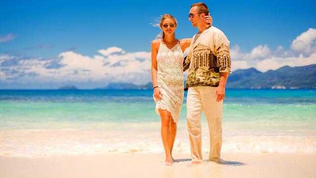 objęta para stoi na plaży przy zejściu do wody w słoneczny dzień
