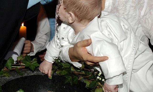 chłopiec trzymany w objęciach nad chrzcielnicą