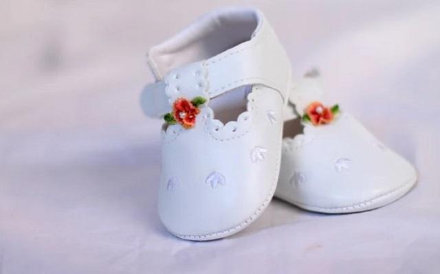 malutkie dziecięce białe buciki z czerwoną aplikacją