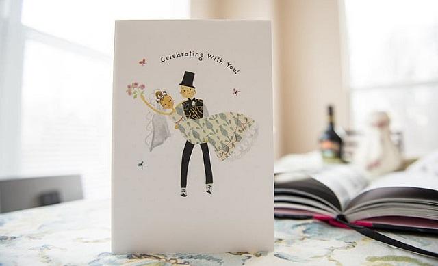 kartka z życzeniami a ilustracjami pary młodej stojąca na stole