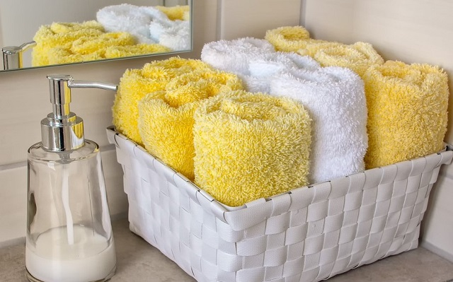 białe i żółte ręczniki w jasnym koszu na blacie w łazience