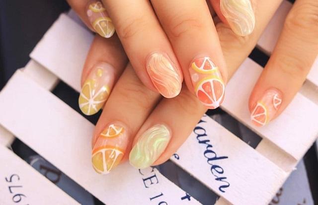 pomarańczowy manicure we wzory na obu dłoniach