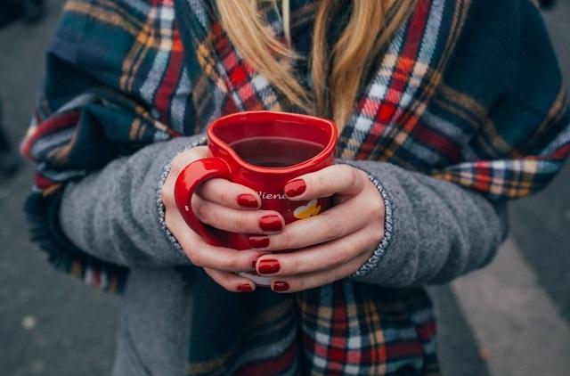 dłonie z czerwonymi paznokciami które trzymają czerwony kubek z kawą