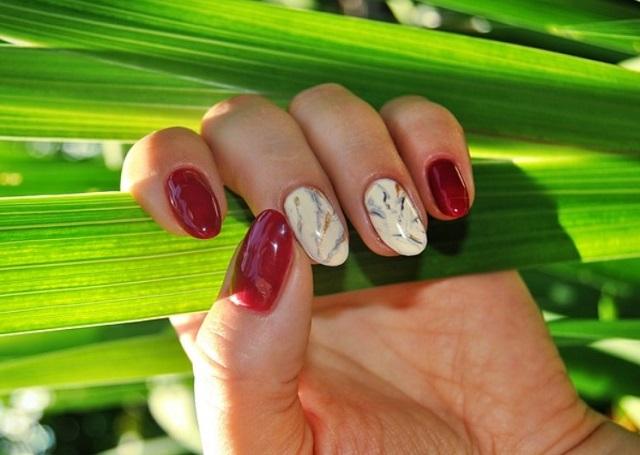 manicure czerwono-biały na dłoni, która trzyma trawę