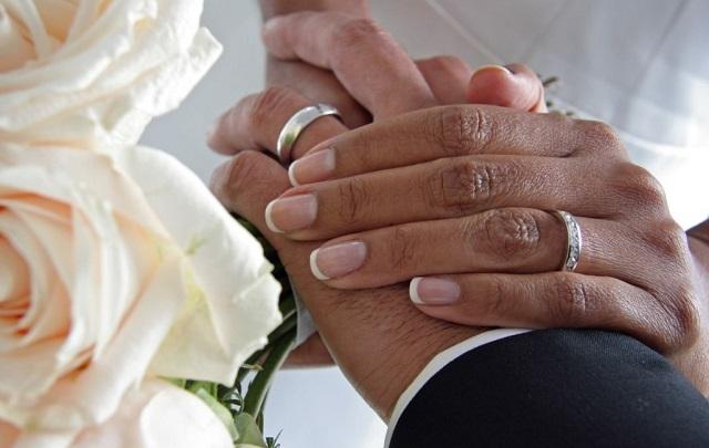 french manicure na jednej dłoni panny młodej, która leży na dłoni męskiej