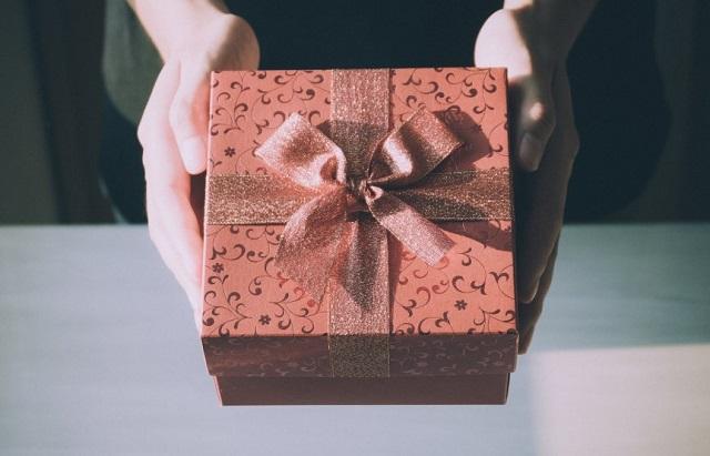 pudełko prezentowe przewiązane kokardą trzymane w dłoniach