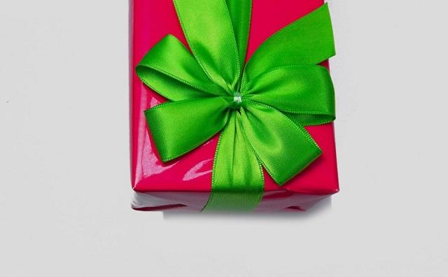 różowe pudełko przewiązane zieloną kokardą